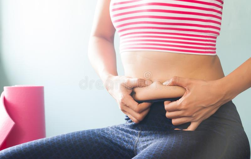 Woman in sport clothing holding excessive belly fat, Healthy and stock photography