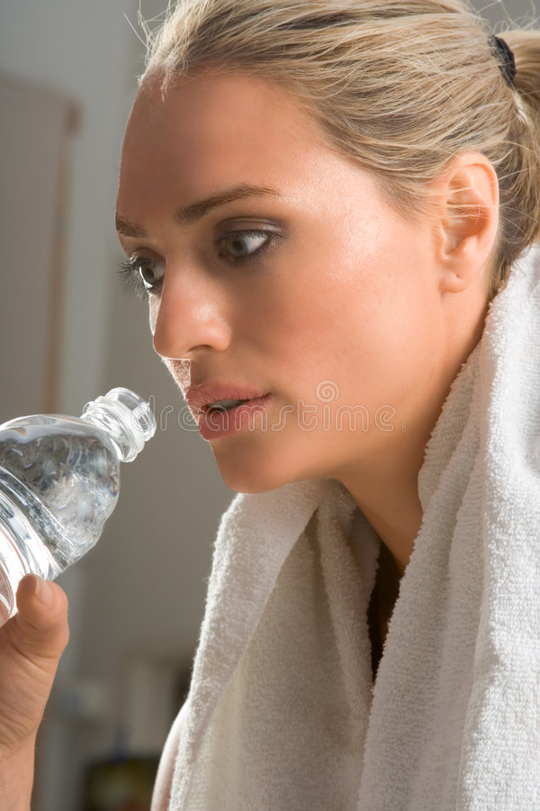 woman with sport drink and towel around in gym stock images
