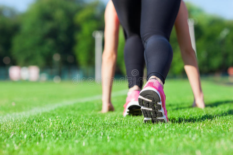 Woman sport run on stadium green grass concept. Fitness girl runner feet in start position closeup on shoe, morning outdoor jog training workout stock photography