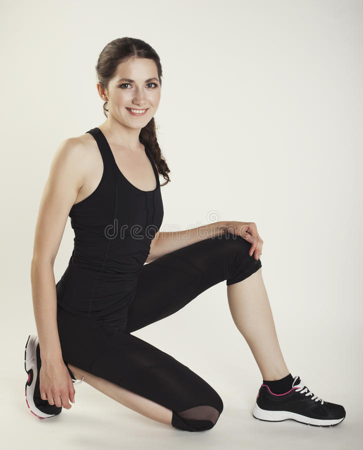 Woman in sport wear siting isolated studio shot. Photo stock image