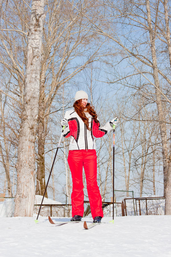 Woman in a sporting suit on skis in-field