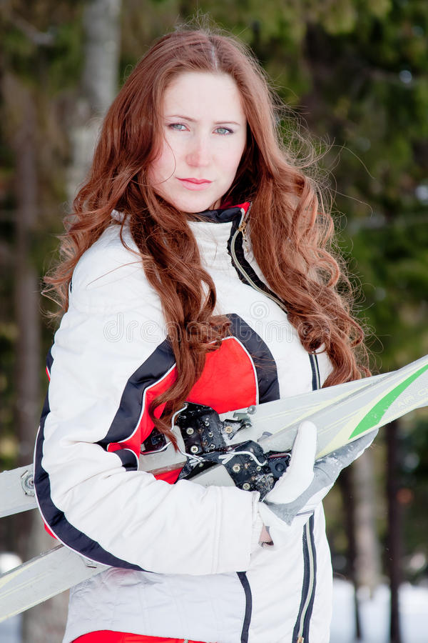 Woman in a sporting suit with skis in-field royalty free stock image