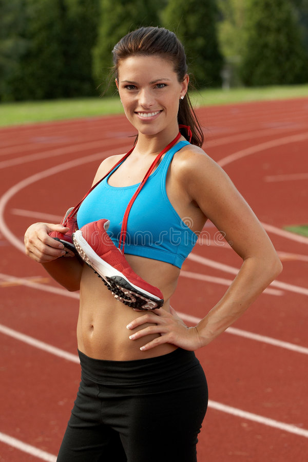 Download Woman In Sports Bra With Running Shoes Tied Around Her Neck Stock Photo - Image: 1403814