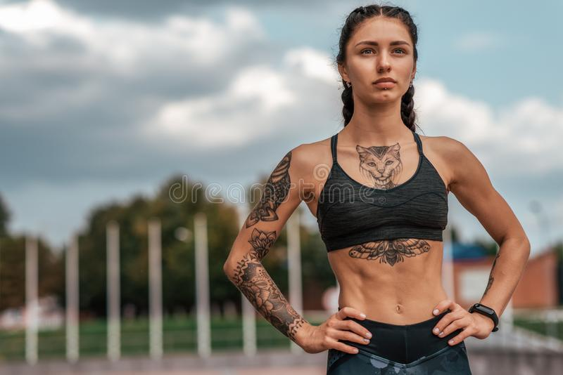 Woman sports coach, summer city, fitness workout. Motivation strength mind thoughts. Tattoo cats on figure. Smart. Bracelet, watch. Free space. Beautiful girl stock images
