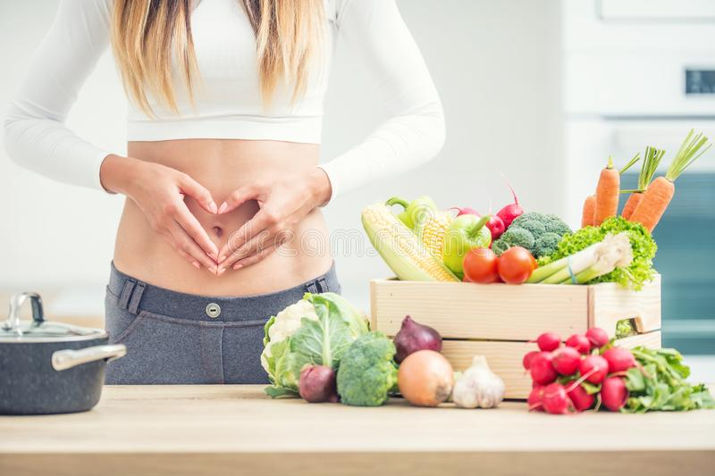 Woman with sports figure on her belly shows heart shape in home kitchen with wooden box full of organic vegetable stock photos