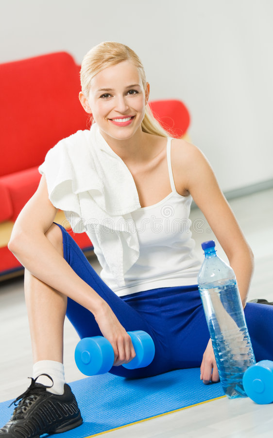 Woman in sportswear. With dumbbells, water and terry towel, indoors royalty free stock image