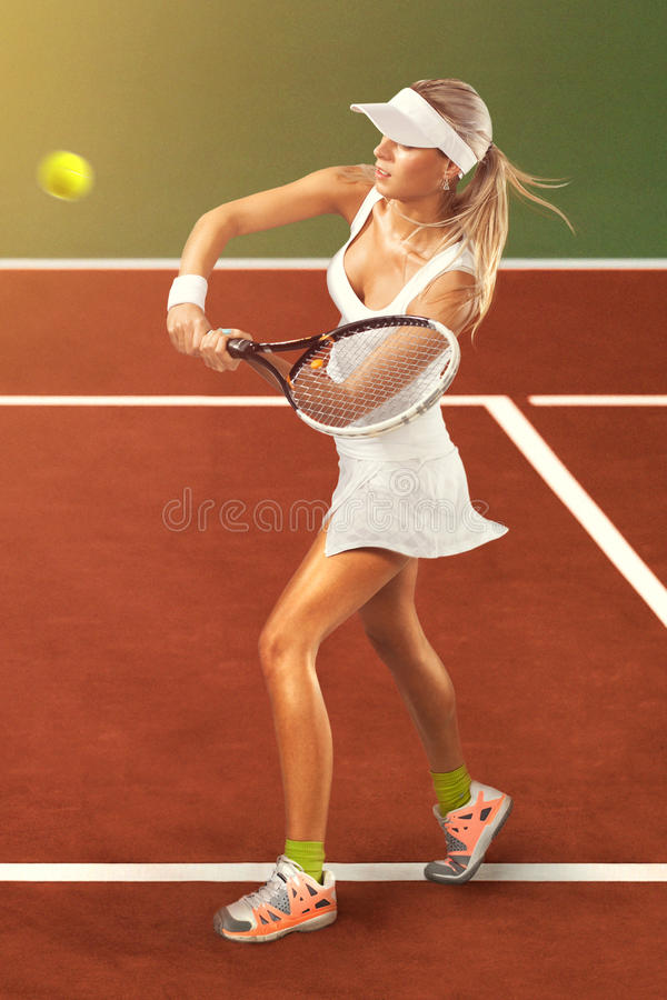Woman in sportswear plays tennis at training. Full length portrait of young woman playing tennis on a dross field. Healthy lifestyle stock images