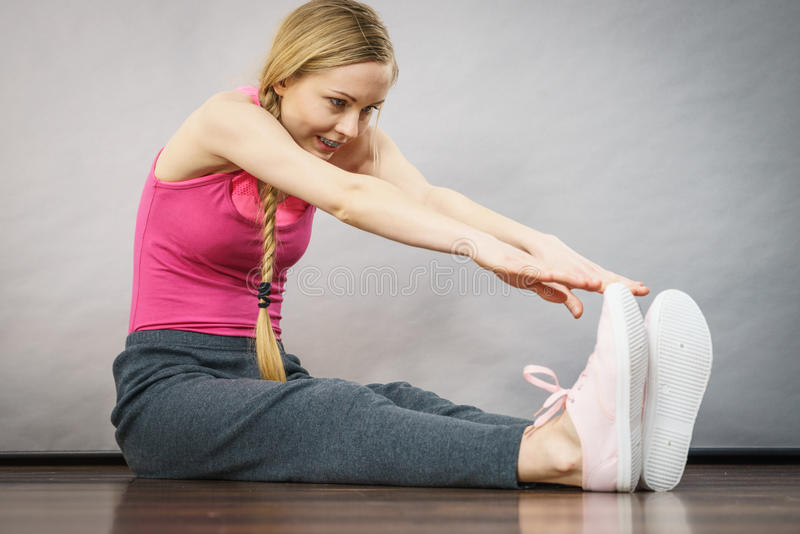 Woman in sportswear stretching legs royalty free stock image