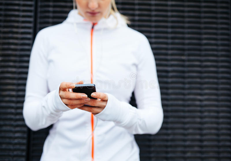 Woman in sportswear using mobile phone. Cropped image of woman in sportswear using mobile phone. Focus on hands and smart phone stock photo