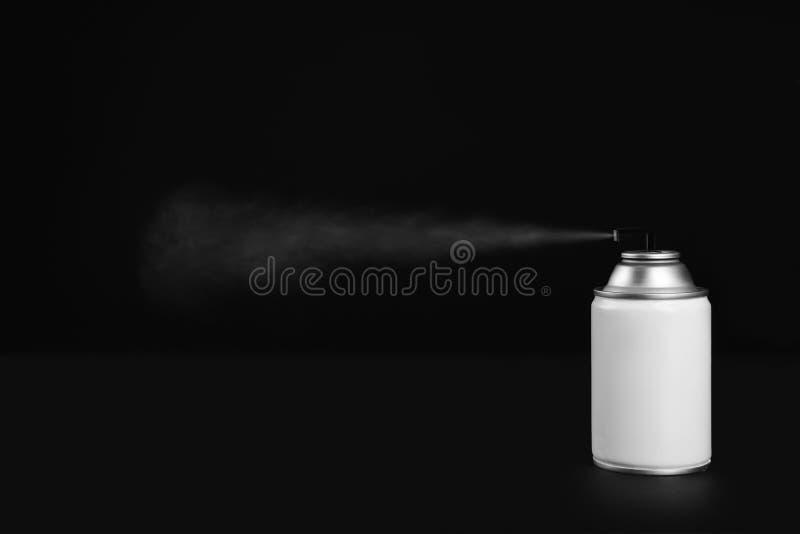Woman spraying air freshener. On black background, closeup stock photography