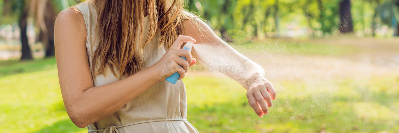 Woman spraying insect repellent on skin outdoor BANNER, long format. Woman spraying insect repellent on skin outdoor. BANNER, long format stock photos