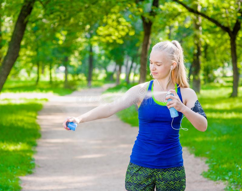 Woman spraying insect repellents on skin before run.  stock photos