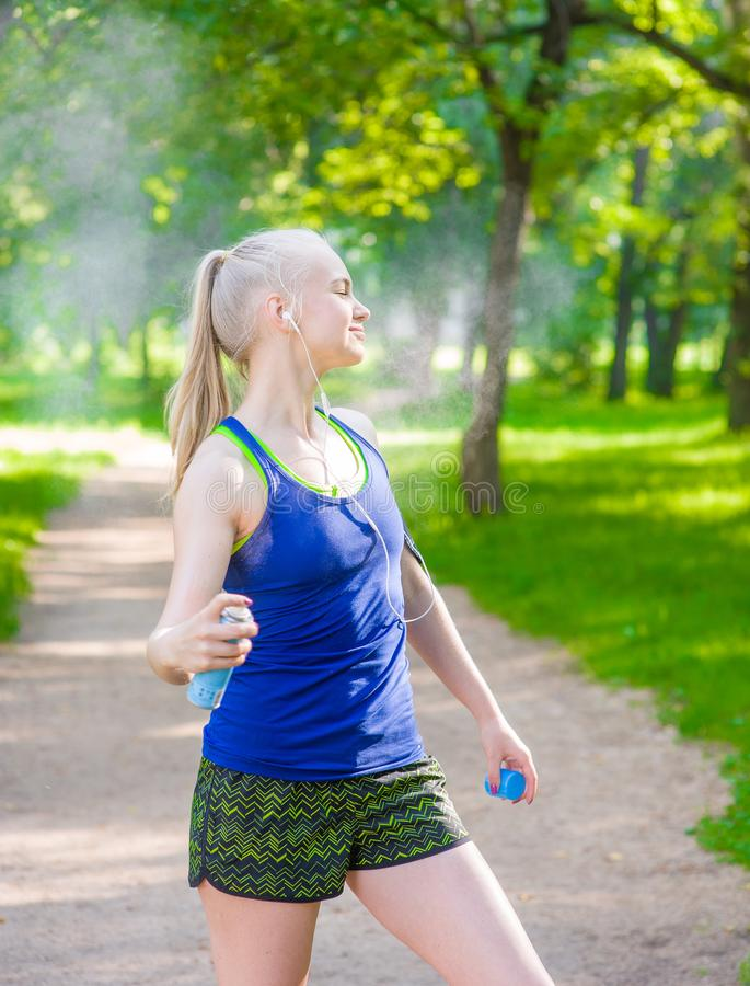 Woman spraying insect repellents on skin before run.  royalty free stock photos