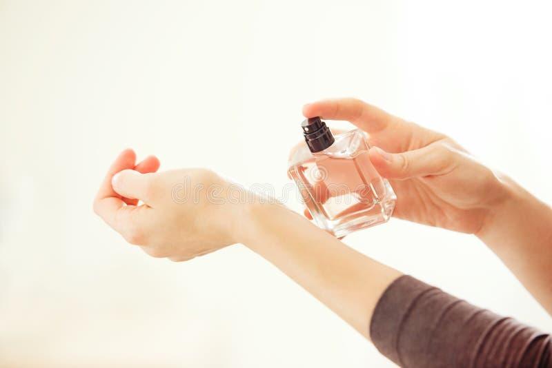 Woman spraying perfume on her wrist.  royalty free stock photos