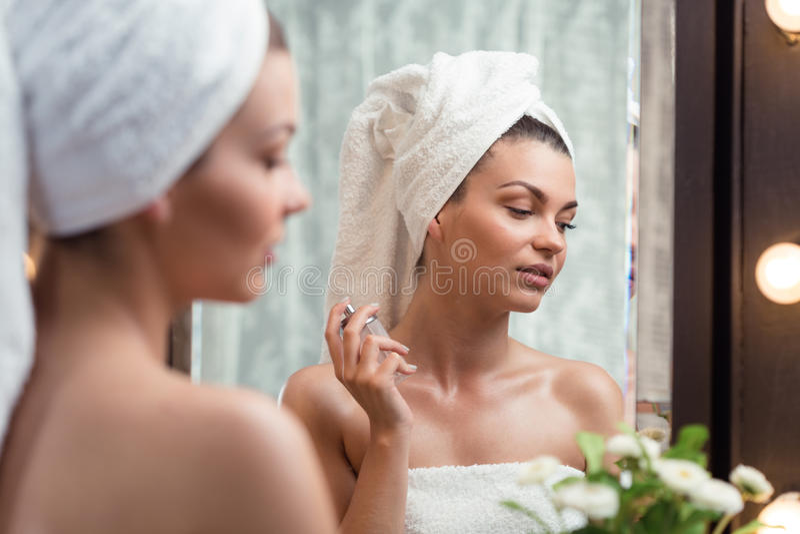 Woman spraying perfume on neck. Naturally beautiful woman spraying perfume on neck skin stock photos