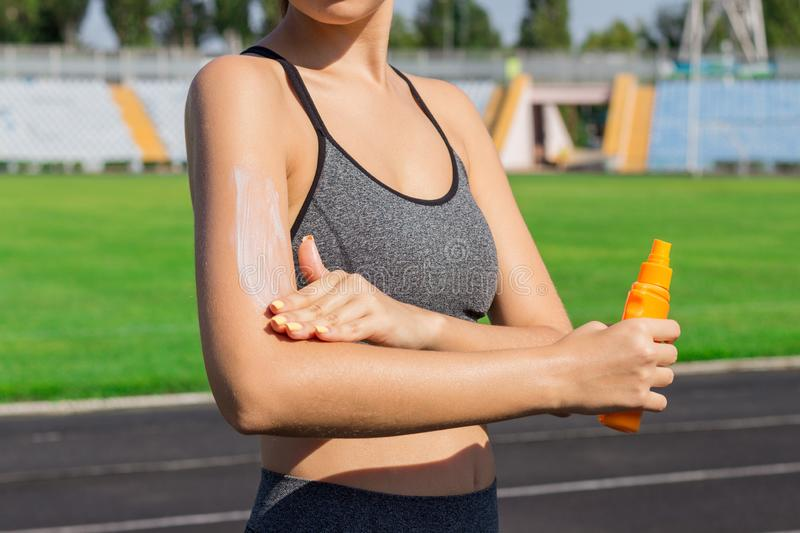 Woman spraying sunscreen cream on skin before run. Sports and healthy concept.  royalty free stock image
