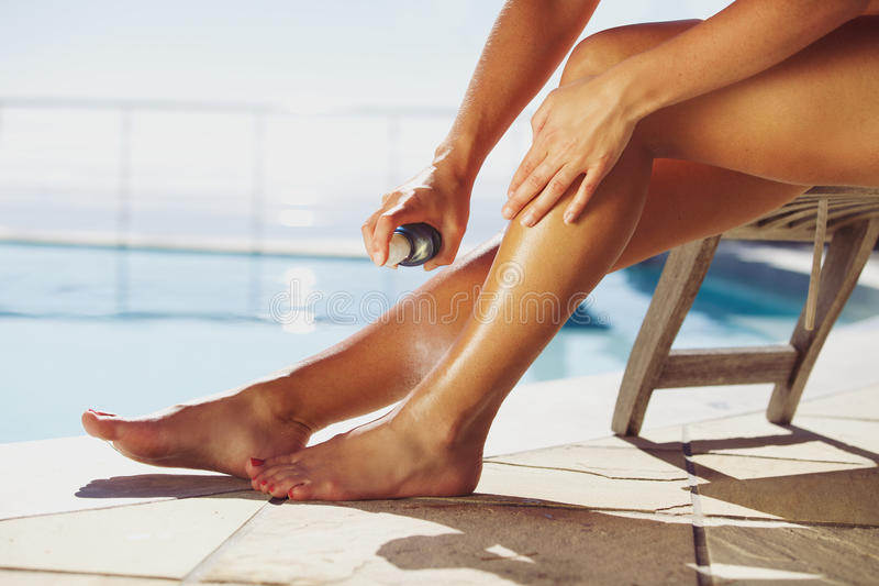 Woman spraying suntan lotion onto her leg by the pool stock images