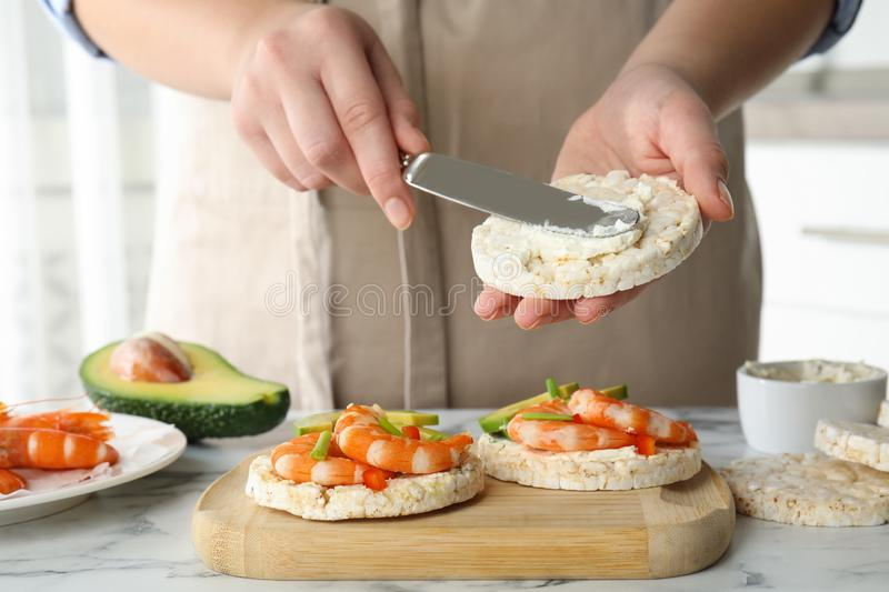 Woman spreading butter on puffed rice cake over table indoors, closeup royalty free stock image