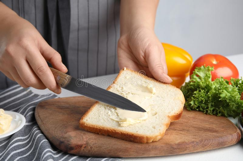 Woman spreading butter on sandwich at table, closeup royalty free stock photography