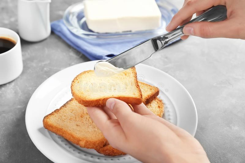 Woman spreading butter on toasted bread at table stock image