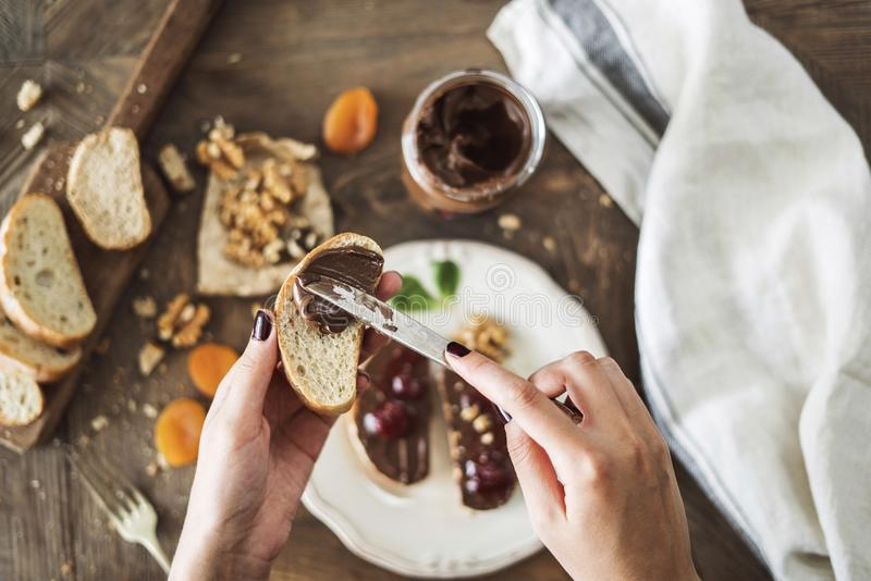 Woman spreading chocolate cream on slice bread stock image