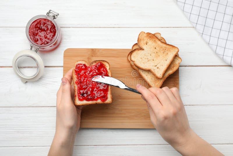 Woman spreading jam on toast stock photography