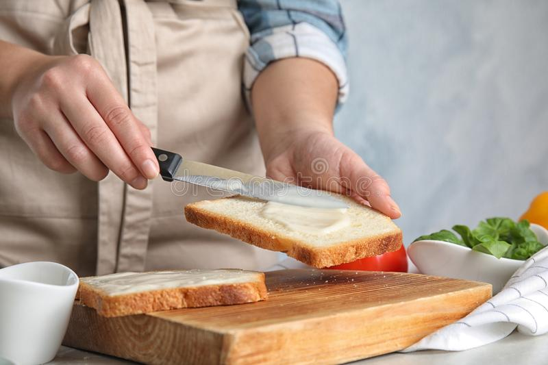 Woman spreading sauce on sandwich at light grey table, closeup royalty free stock photo
