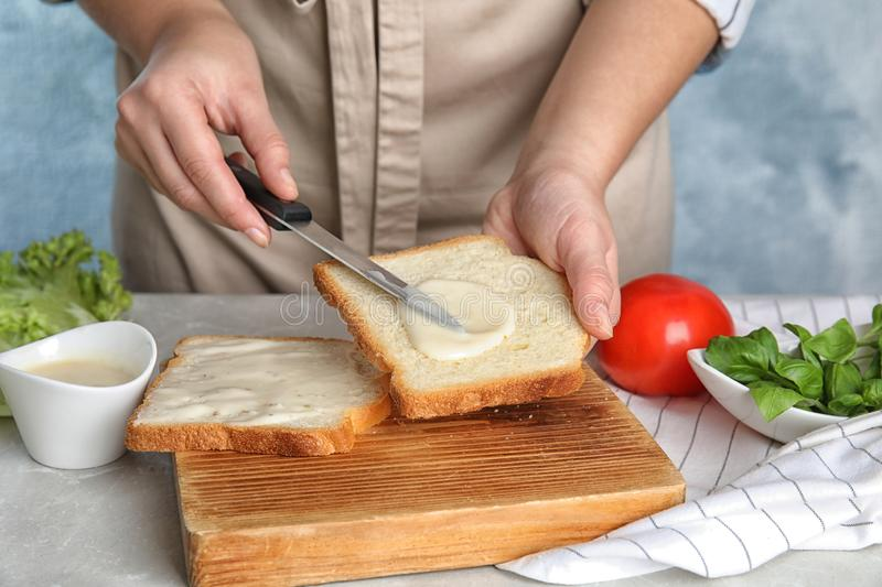 Woman spreading sauce on sandwich at grey marble table, closeup royalty free stock photos
