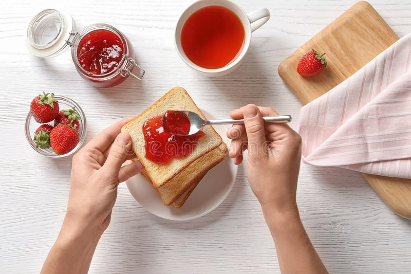 Woman spreading strawberry jam on toast bread stock image