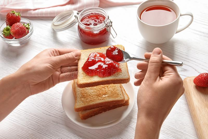 Woman spreading strawberry jam on toast bread royalty free stock images