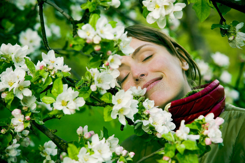 Woman in Spring. Young woman smelling white flowers or blossoms on tree