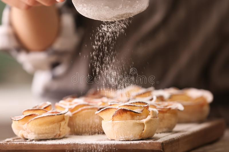 Woman sprinkling apple roses from puff pastry with sugar powder in kitchen, closeup royalty free stock images