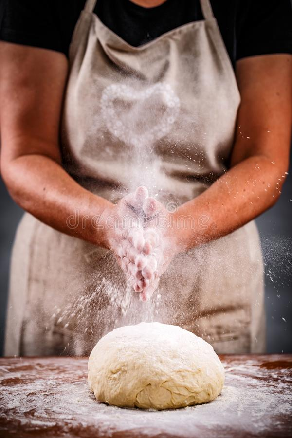 Woman sprinkling flour stock photography