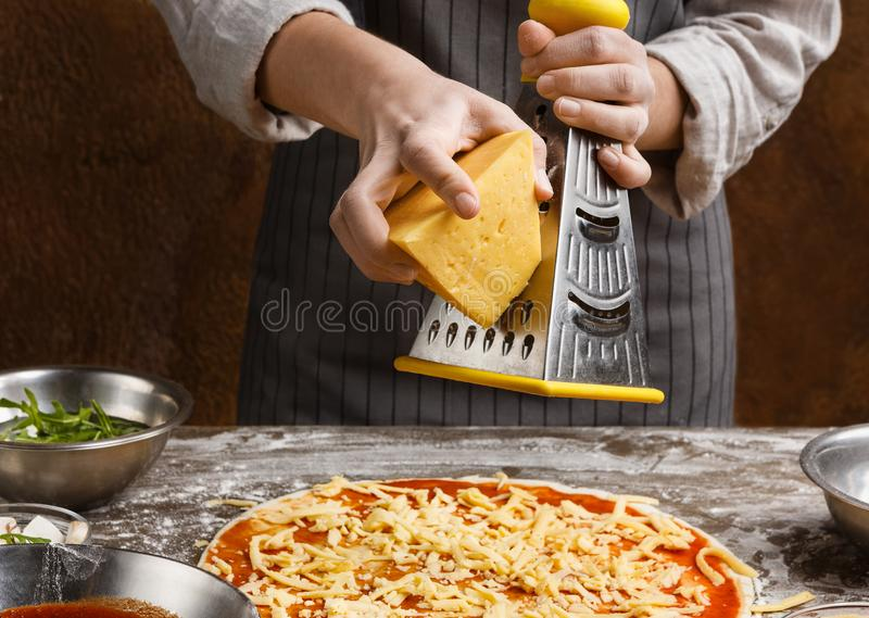 Woman sprinkling pizza with cheese, rubbing on grater stock image