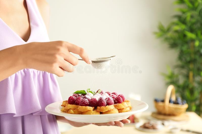 Woman sprinkling tasty homemade waffles with sugar powder, closeup royalty free stock images