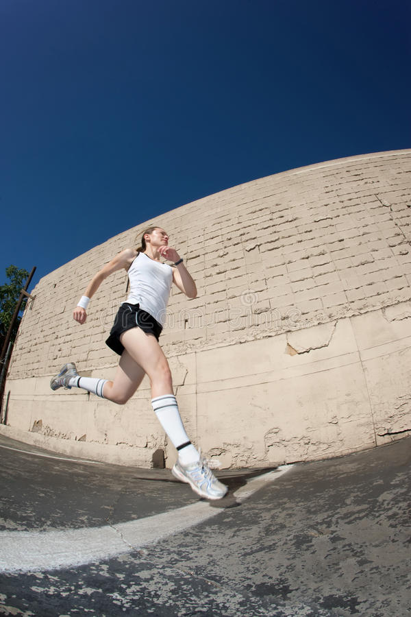 Woman Sprints Towards The Finish Line. Royalty Free Stock Images