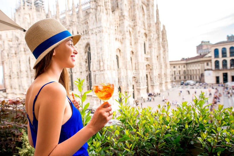 Woman with spritz aperol drink in Milan. Young woman standing with traditional italian alcohol drink spritz aperol on the terrace with great view on Duomo stock image