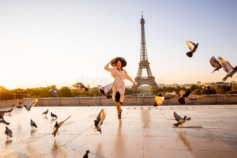 Woman on the square with beautiful view on the Eiffel tower in Paris. Woman running on the famous square dispersing pigeons with great view on the Eiffel tower stock photos