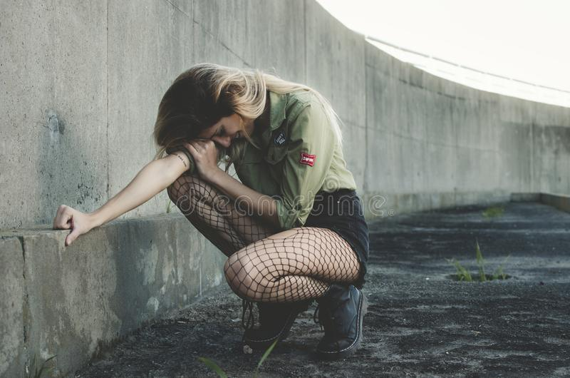 Woman Squatting Near Gray Concrete Wall at Daytime stock photos