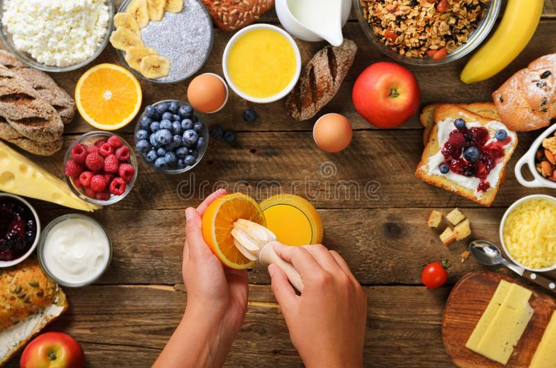 Woman squeezing orange fruit and making juice. Girl cooking breakfast. Healthy breakfast ingredients, food frame royalty free stock image