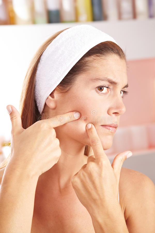 Woman squeezing pimple. Woman in bathroom squeezing pimple on her cheek stock photos