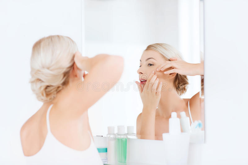 Woman squeezing pimple at bathroom mirror. Beauty, hygiene, skin problem and people concept - young woman looking to mirror and squeezing pimple at home bathroom stock images
