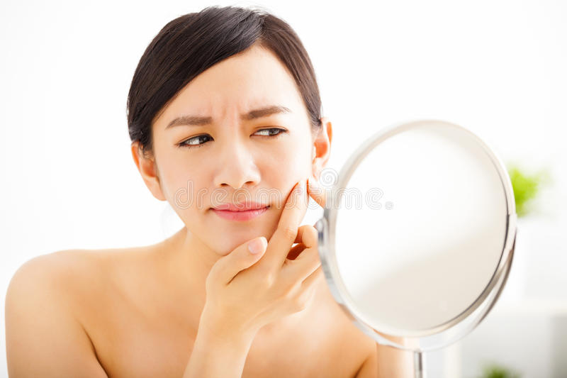 Woman Squeezing pimple looking on mirror. Young woman Squeezing pimple looking on mirror stock photos