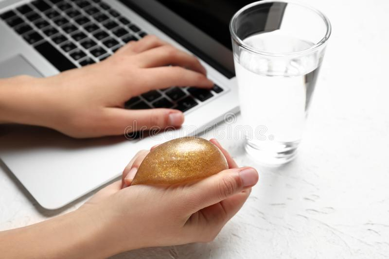 Woman squeezing stress ball while working with laptop stock photography