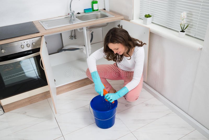 Woman Squeezing Wet Rag At Kitchen Room. Young Woman Squeezing Wet Rag In Blue Bucket At Kitchen Room stock photography