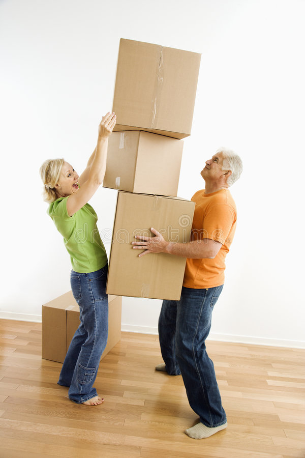 Woman stacking boxes. Middle-aged man holding stack of cardboard moving boxes while woman places another one on royalty free stock image