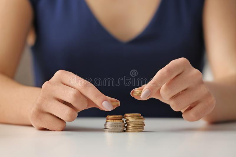 Woman stacking coins on table. Savings concept royalty free stock photo