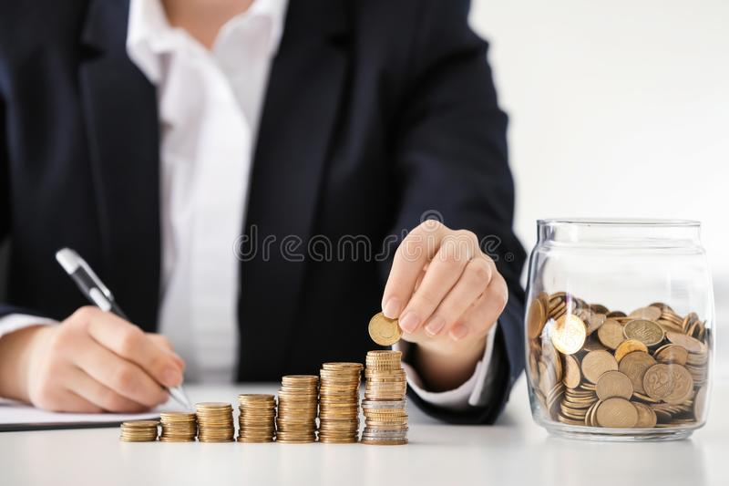 Woman stacking coins on table. Savings concept royalty free stock photography