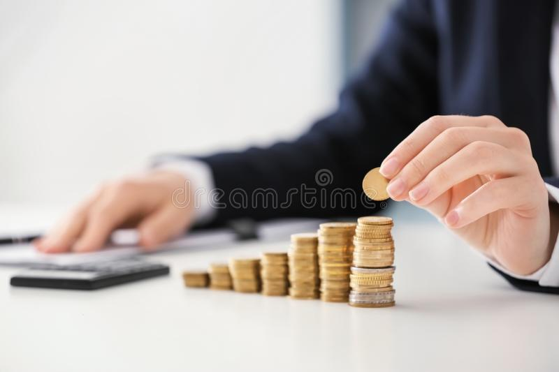 Woman stacking coins on table. Savings concept royalty free stock photos