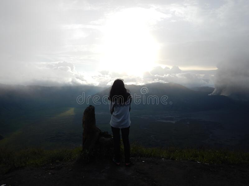 Woman Staing at the Edge of the Mountain Facing the Sun stock photo
